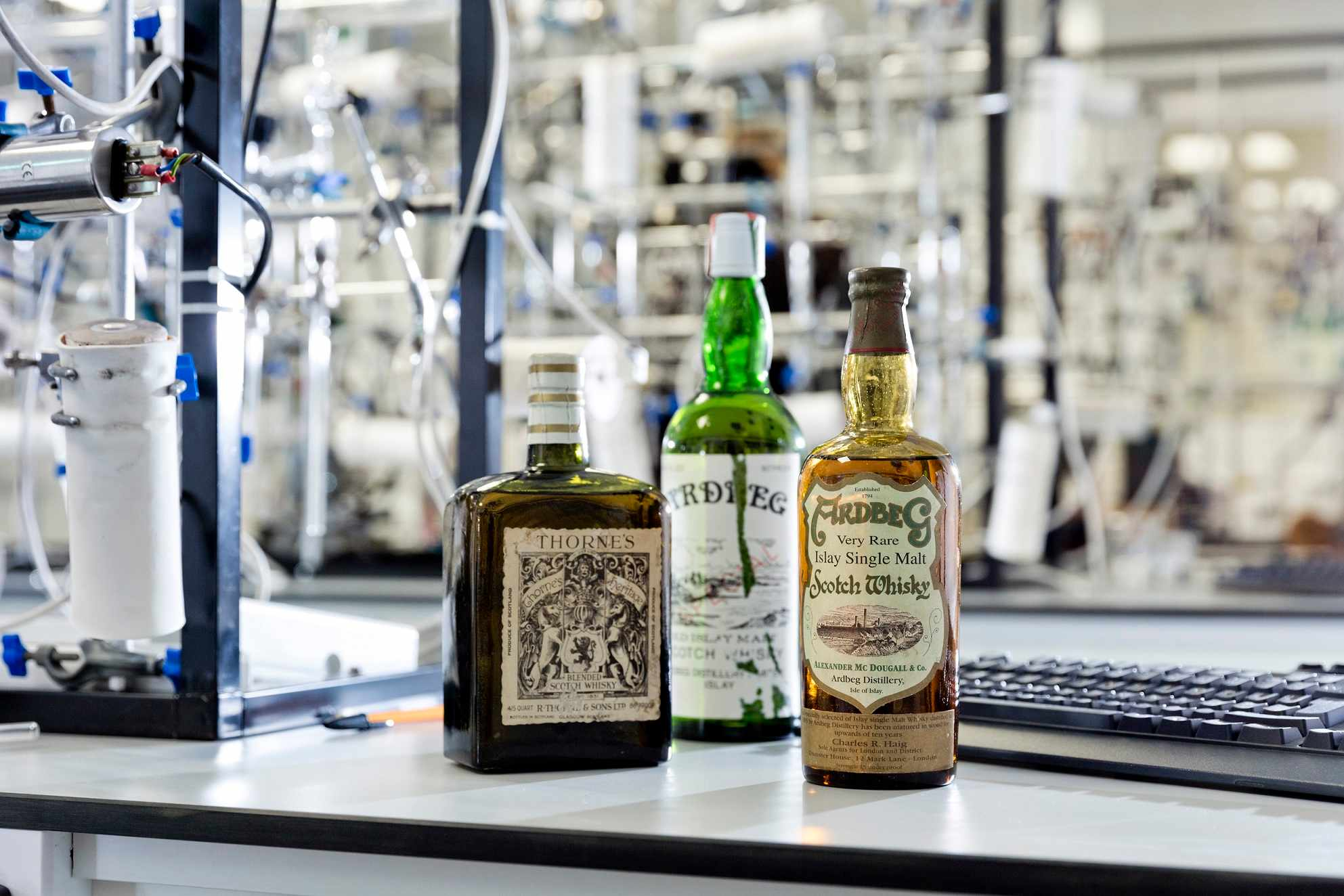 three whisky bottles on lab bench
